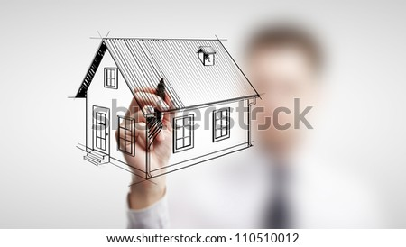 businessman drawing cottage on a white background