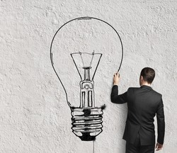 businessman drawing lamp on wall