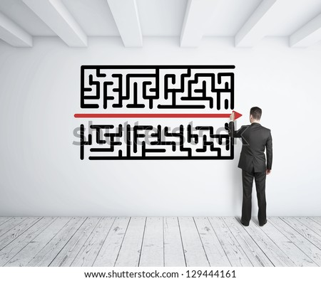 businessman drawing maze on white wall