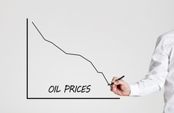 Businessman draws a declining line graph with the word oil prices. decrease in oil prices concept.