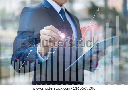 Businessman draws a graph of financial statistics on a blurred background. #1165569208