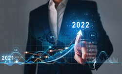 Businessman draws  increase arrow graph corporate future growth year 2021 to 2022.   Development to success and motivation.