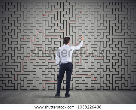 Businessman draws the solution of a labyrinth. Concept of problem solving #1038226438