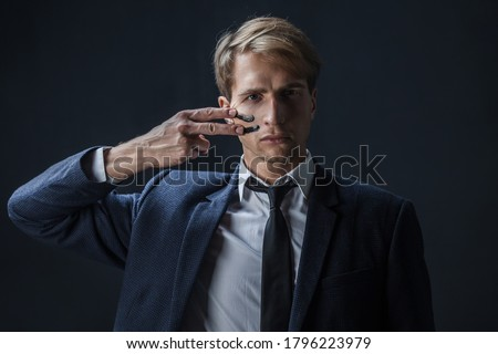 businessman draws two stripes on his cheeks, war paint. Competition in business, concept. A young man in a suit and tie makes war paint on his face
