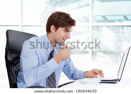 businessman drink coffee or tea hold cup sitting at desk in office using laptop computer, handsome young business man happy smile