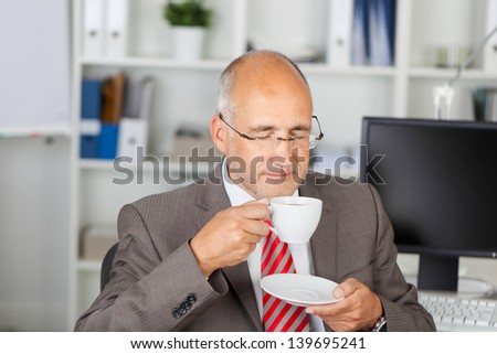 businessman drinking a cup of coffee in the office