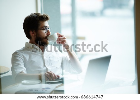 Businessman drinking coffee while thinking of new project