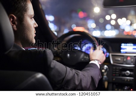 businessman driving a car at night
