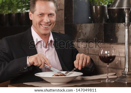 Businessman eating. Confident men in formal wear eating at the restaurant and smiling at camera