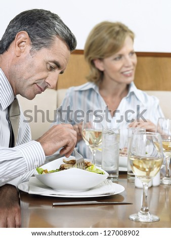 Businessman eating food with woman smiling in background