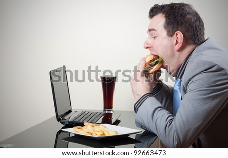 Businessman eating junk food while working