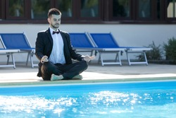 Businessman enjoying the relaxing time in the pool with suit on.
