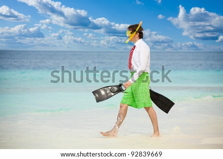 Businessman entering the ocean waters wearing snoring mask with flippers and wearing formal clothes with red tie entering water on the beach