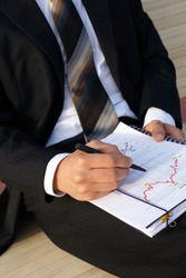 Businessman evaluates company data and checks charts and values