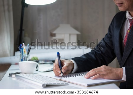 Businessman examines a contract and writing on notebook vintage tone.