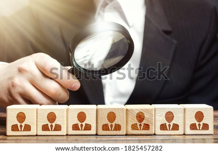 Businessman examines a magnifying glass blocks with employees. Analysis of company's work, optimization of personnel and costs. Checking for professional suitability of workers. Hiring and recruiting. Stock fotó ©