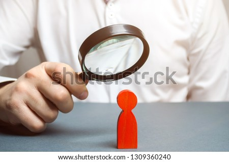 Businessman examines a red man through a magnifying glass. Search for unreliable employee. Weak link. Diagnosis of psychological and physical diseases. Toxicity in the staff of workers. Sabotage
