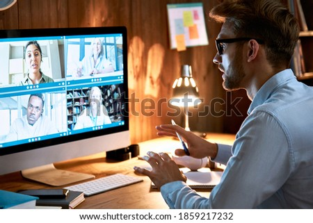Businessman executive leading virtual team meeting on video conference call using computer working from home office talking to diverse colleagues in remote videoconference online social distance chat.