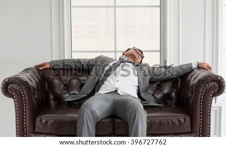 Businessman exhausted and tired from overtime working, He sit and sleep on brown leather sofa.