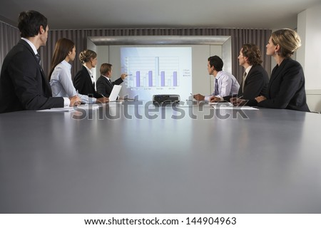 Businessman explaining bar chat to colleagues at conference table
