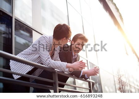 Businessman explains something to businesswoman on balcony #616893248