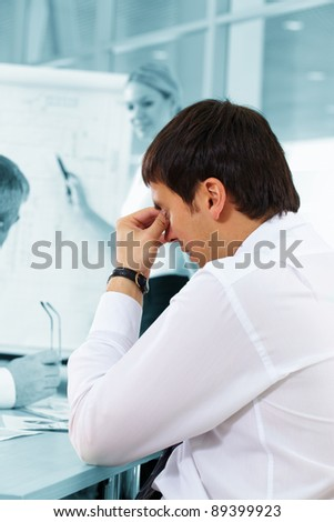 Businessman expressing tiredness during the meeting