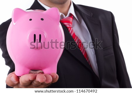Businessman extends pink piggy bank, depth of field, isolated on white.