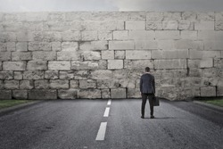 Businessman facing a big stone wall