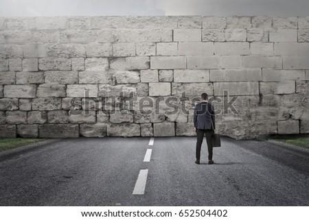 Businessman facing a big stone wall Stock photo ©