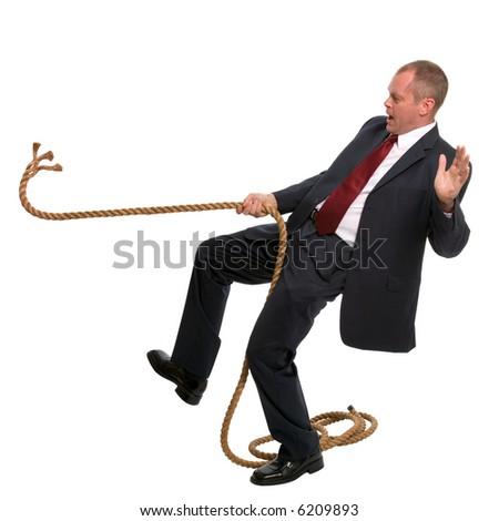 Businessman falling as the rope he was pulling breaks.