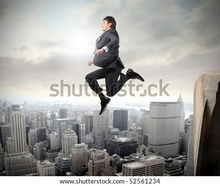 Businessman falling from a skyscraper over a city