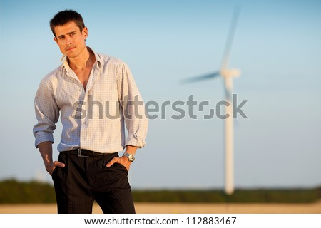 businessman (farmer) standing in a wheat field over background of blue sky and white wind turbine with hands in pockets and wheat spikelet in mouth