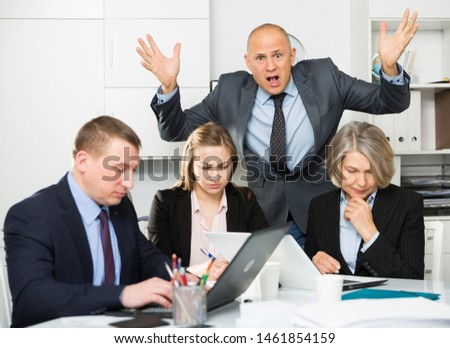 Businessman feeling angry to coworkers in office