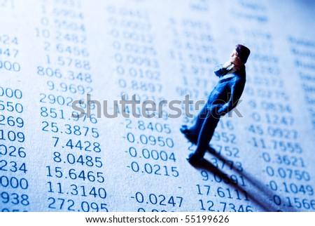 businessman figurine standing on a financial data report