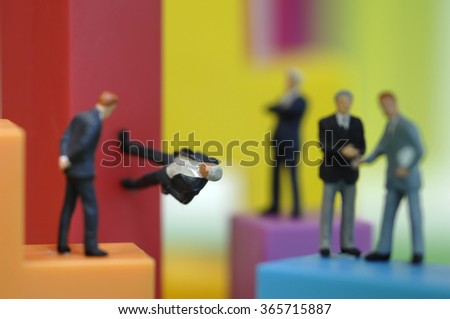 Businessman figurines on bright building bricks, close up
