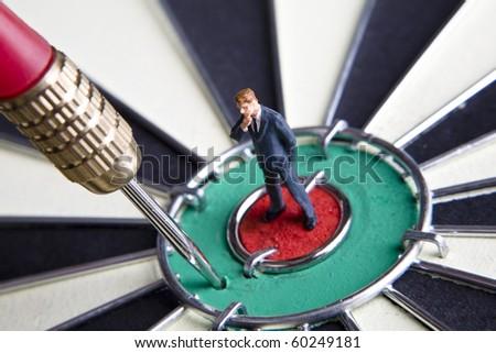 Businessman figurines placed on a dartboard