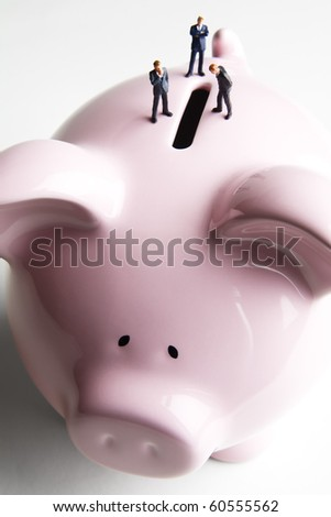 Businessman figurines placed on a piggy bank