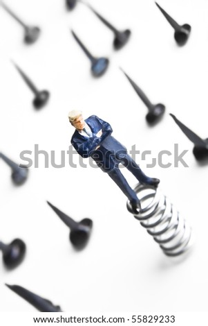 Businessman figurines standing on springs surrounded by tacks