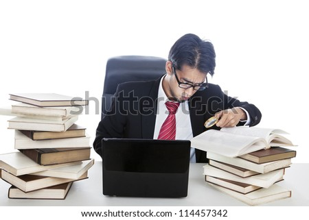 Businessman finding information from textbooks using magnifying glass. shot in studio - stock photo
