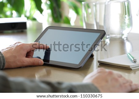 Businessman finger pointing to the screen of a tablet-pc