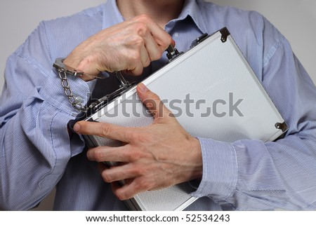 Businessman firmly holding a metal briefcase handcuffed to his wrist