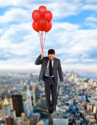 Businessman flying high with helium balloons.
