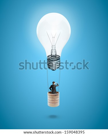businessman flying in air balloon with bulb