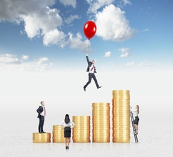 Businessman flying on a red baloon over a bar chart made of coins, another man standing on the lowest bar, woman climbing a ladder, another woman looking at them. Sky background. Concept of success.