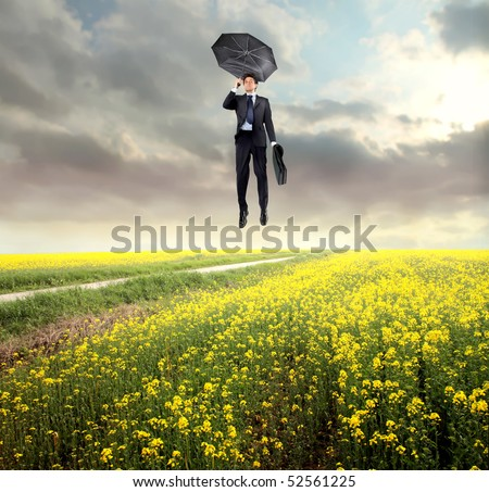 Businessman flying over a green meadow