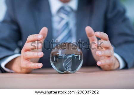 Businessman forecasting a crystal ball in the office #298037282