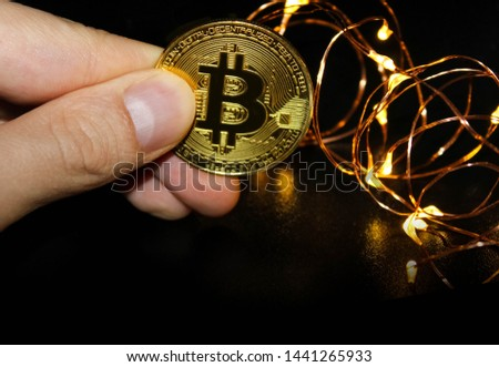Businessman get money form Bitcoin,Businessman Holding Bitcoin on black background,Blockchain transfers concept #1441265933