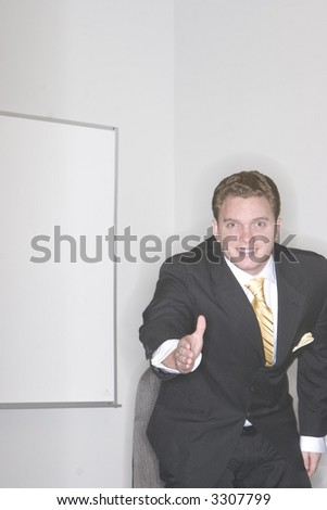 Businessman gets up out of his chair and gives a warm handshake