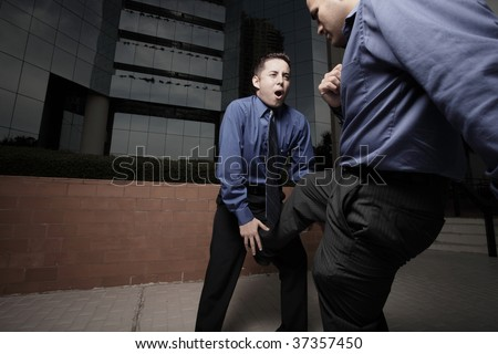 Businessman getting his groin kicked by another businessman