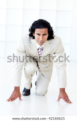 Businessman getting ready for a race against white background